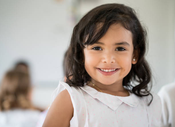 Portrait of a Latin American girl looking very happy Portrait of a beautiful happy Latin American girl at the school looking at the camera smiling children only stock pictures, royalty-free photos & images