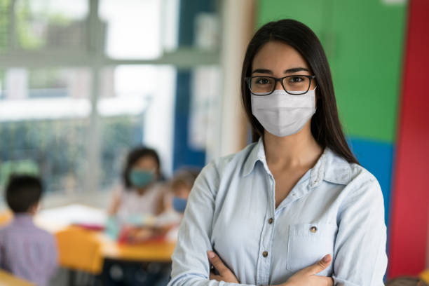 Portrait of a  Latin American teacher at the school wearing a facemask stock photo