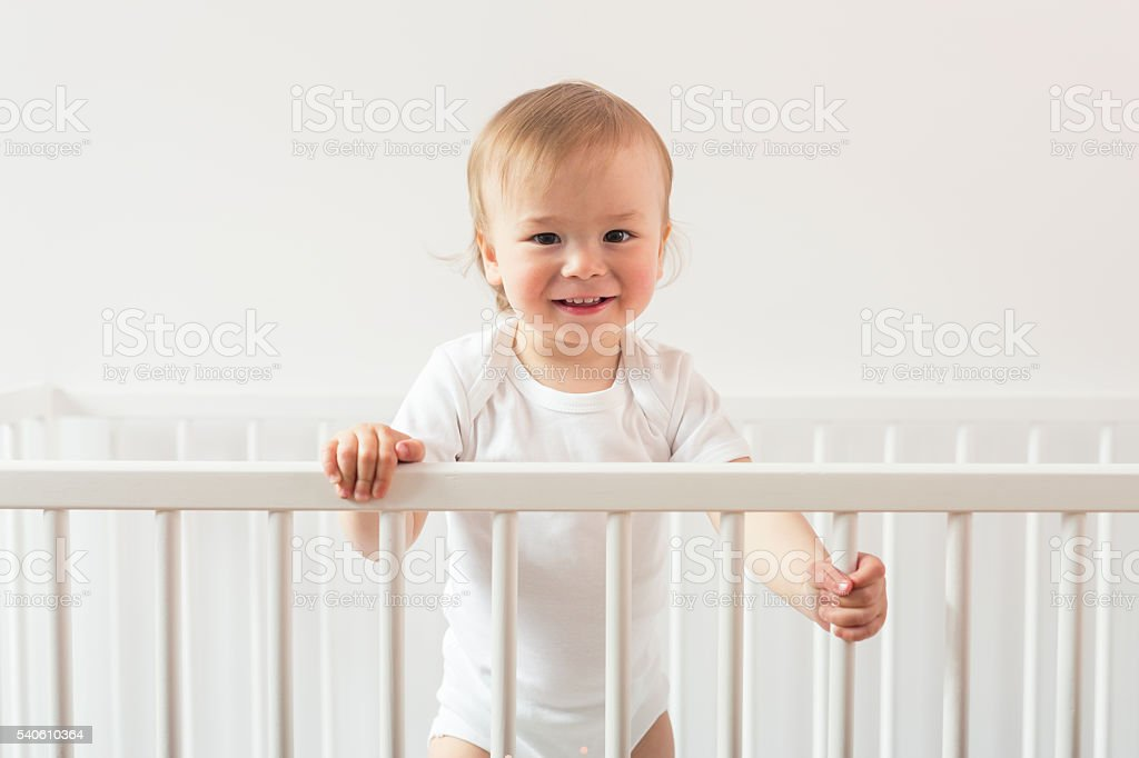 Portrait of a laughing baby standing in a crib. stock photo