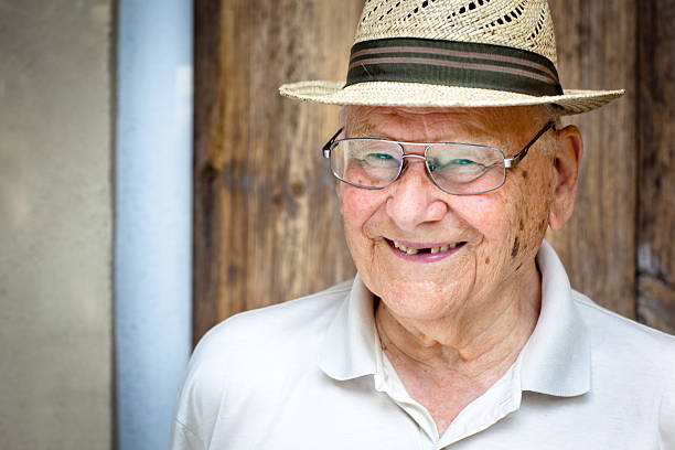 portrait of a laughing senior man with a straw hat​​​ foto