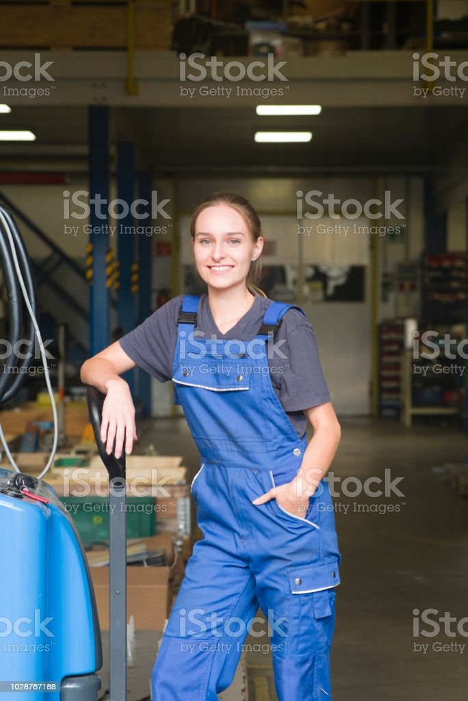 Portrait of a young blond women in metal industry leans at pallet...