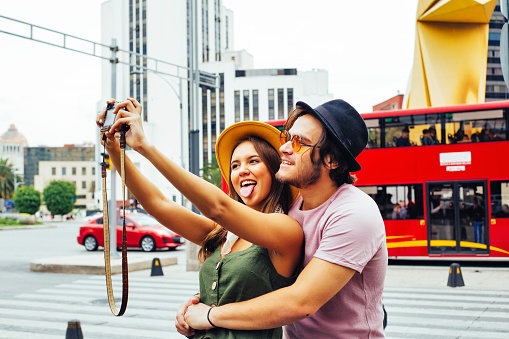 Portrait of a laughing young couple having fun taking selfie on street of Mexico City center near Caballito de la Loteria