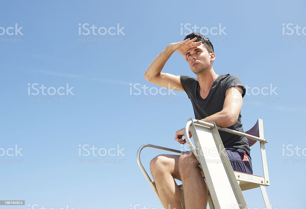Portrait of a lifeguard sitting in chair on summer day royalty-free stock photo