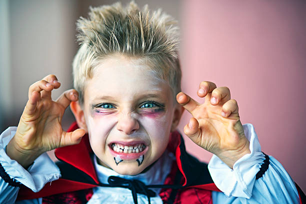 Portrait of a little boy dressed up as halloween vampire Portrait of a little boy dressed up as halloween vampire. The boy is aged 6 and is making scary face at the camera. costume stock pictures, royalty-free photos & images