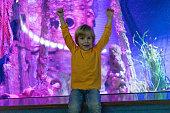 Portrait of a little boy in an aquarium.