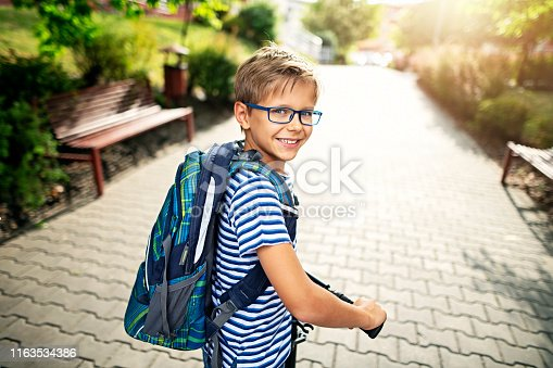 Little boy wearing backpack is riding to school on his push scooter. Nikon D850