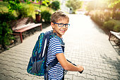 Little boy wearing backpack is riding to school on his push scooter.\nNikon D850