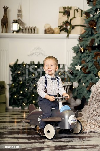 486524205 istock photo Portrait of a little boy sitting on a vintage toy airplane near a Christmas tree. Christmas decorations. The boy rejoices at his Christmas present. Merry Christmas and happy New Year 2020 1183454181
