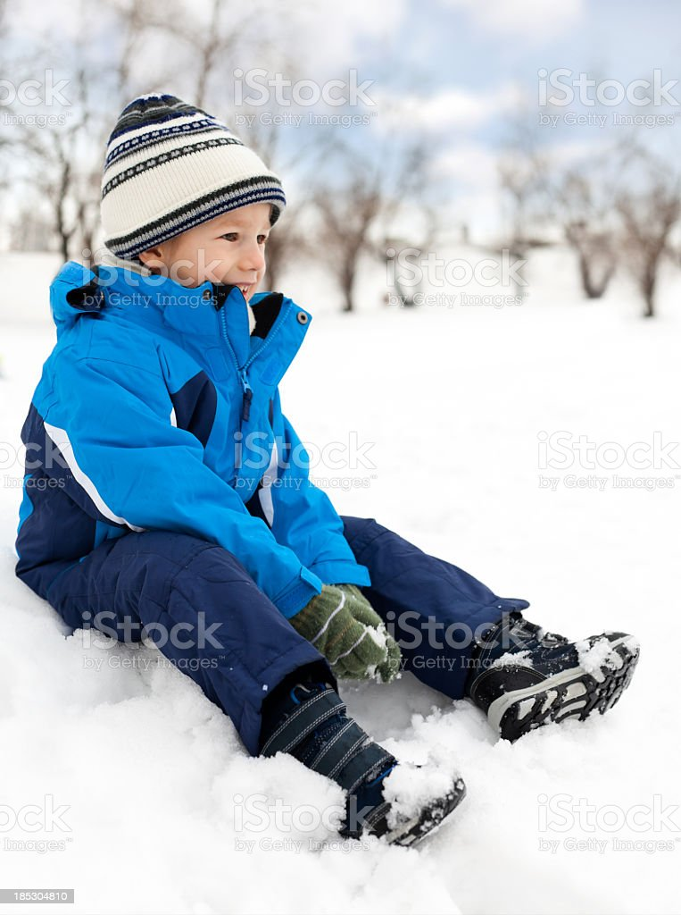 Portrait of a little boy sitting on the snow royalty-free stock photo