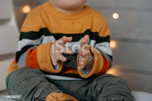 Little boy with down syndrome holds buns with poppy seeds.  He lookes interested and surprised. He is v ery emotional and funny. Child wears yellow sweater and looks elegant.