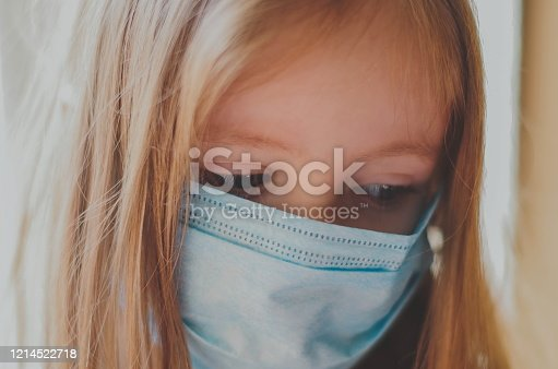 Close up portrait of a little girl in a medical mask. home quarantine