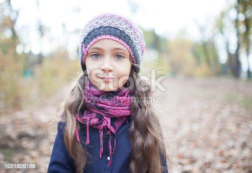 istock Portrait of a little girl in autumn park 1051826188