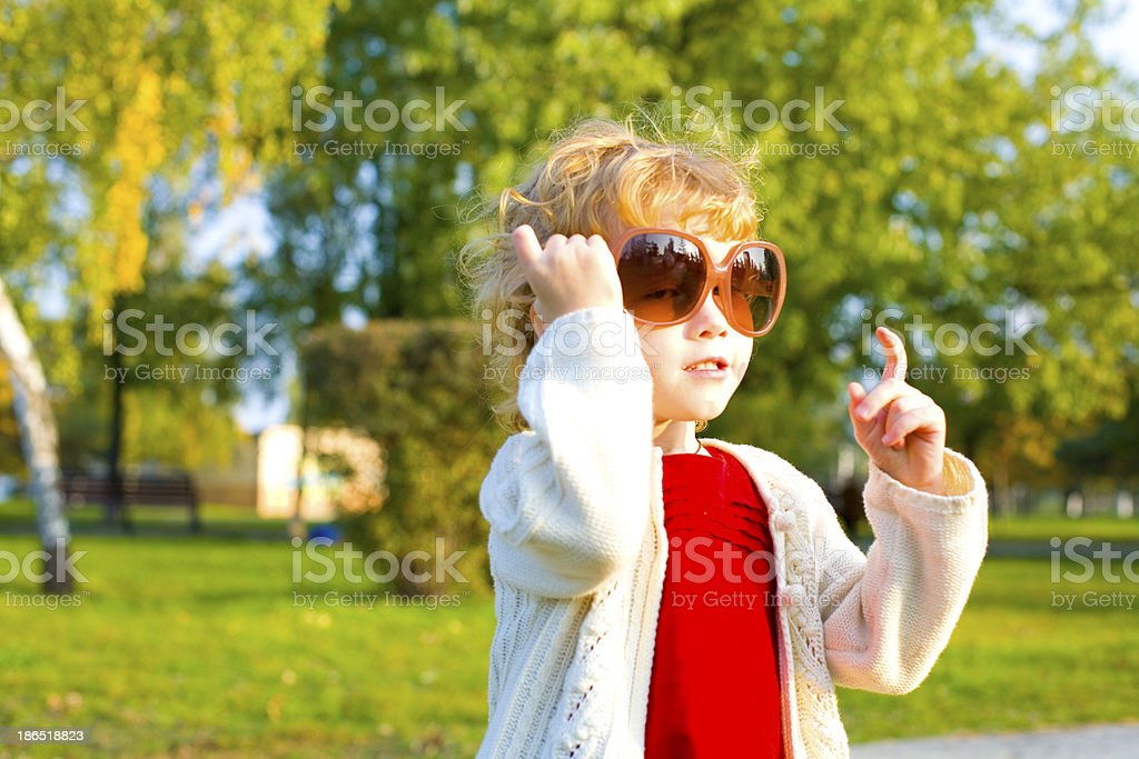 Portrait of a little girl playing in big sunglasses outdoors royalty-free stock photo