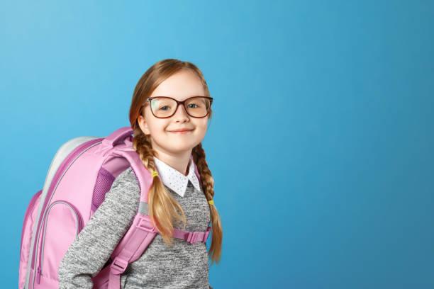 porträt eines kleinen mädchens schulmädchen mit einem rucksack auf blauem hintergrund. zurück zur schule. das konzept der bildung. platz kopieren. - liebeskind umhängetasche stock-fotos und bilder