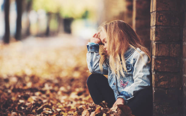 Sad Young Girl At Green Bushes Background Stock Photo