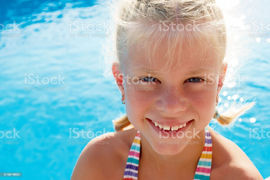 Portrait of a little girl vacationers beside swimming pool. stock photo