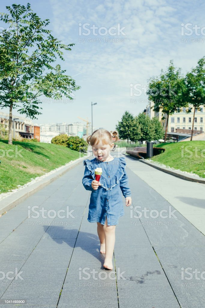Portrait of a little girl walking with ice cream stock photo