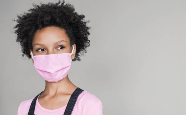 Portrait of a little girl wearing protective face mask looking up stock photo