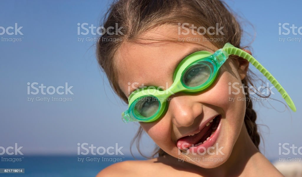 Portrait of a little girl who grimaces with underwater glasses stock photo