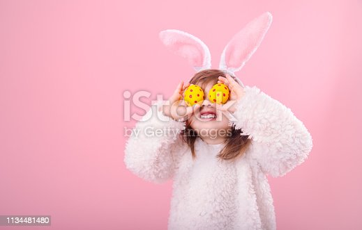Portrait of cute little girl with Bunny ears and yellow Easter eggs in red polka dots, closes eyes with testicles, isolated on pink background