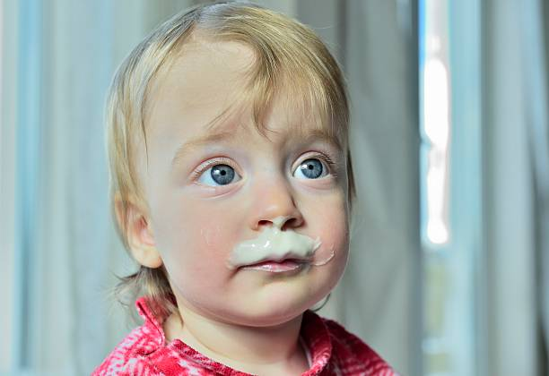 Portrait of a little girl with milk moustaches. stock photo