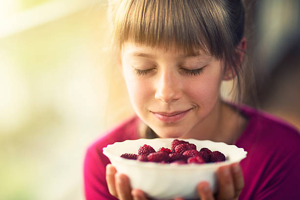 Portrait of a little girl with raspberries. stock photo