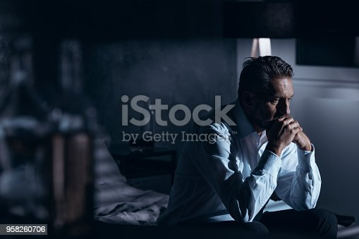 istock Portrait of a lonely mature man with depression sitting on a bed in a gray room with bottles of alcohol standing around 958260706