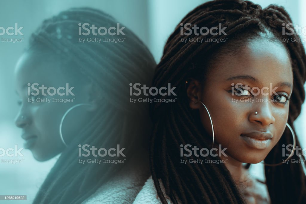 Portrait of a lovely African girl A portrait of admirable young black female from Guinea-Bissau with big earrings, nose piercing, and braided hair, she is leaning against an outdoor glass surface which fully reflects her African-American Ethnicity Stock Photo