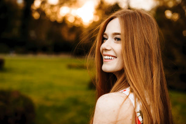 Portrait of a lovely female with long red hair and freckles looking away laughing against sunset outside. stock photo