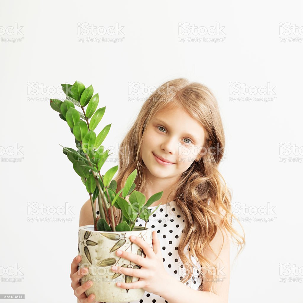 Portrait of a lovely little girl with green houseplant stock photo