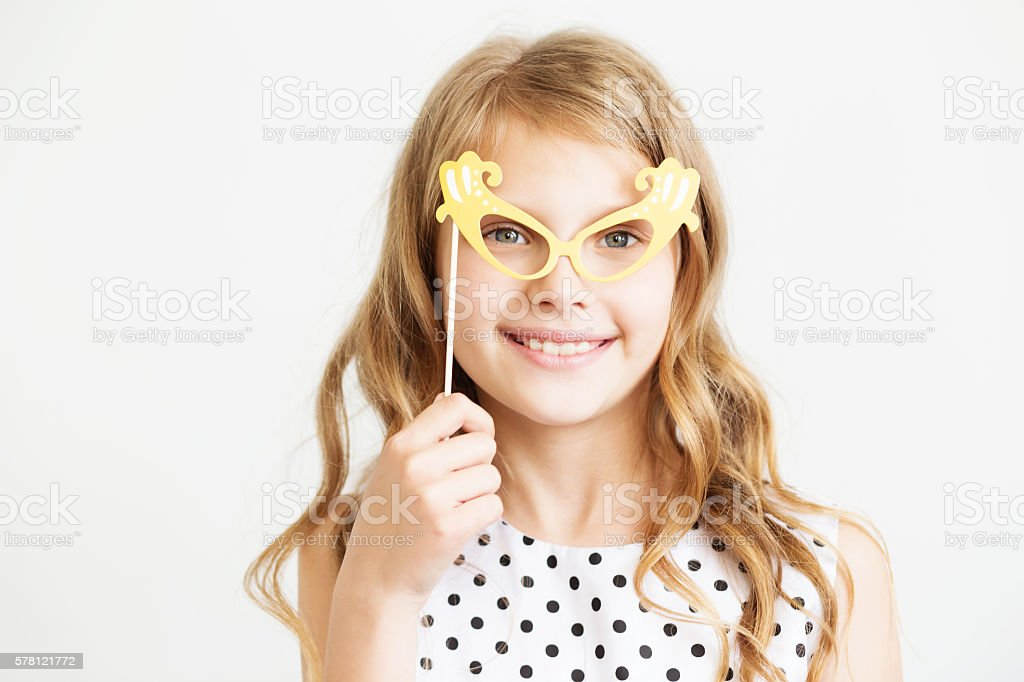 Portrait of a lovely little girl with party paper glasses stock photo