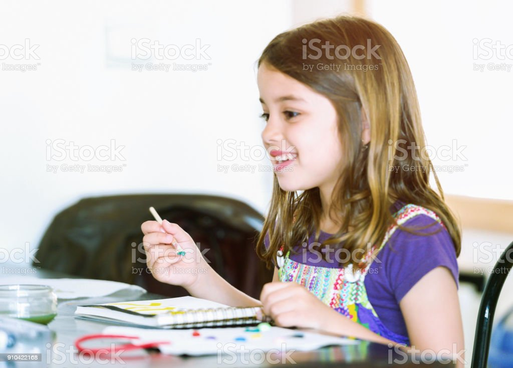 Portrait of a lovely smiling girl painting a picture stock photo