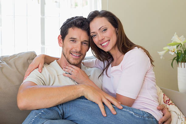 portrait of a loving couple sitting on couch - 30 39 years stock photos and pictures