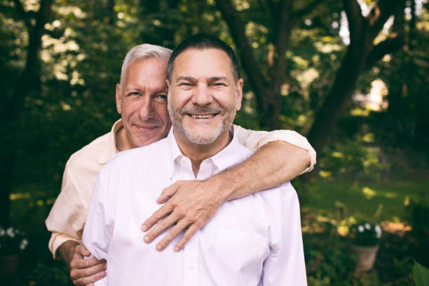 portrait of a loving middle-aged gay couple portrait of a loving middle-aged gay couple surrounded by nature. gay couple stock pictures, royalty-free photos & images