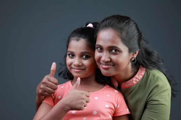 Portrait of a loving mother and daughter showing thumbs up stock photo