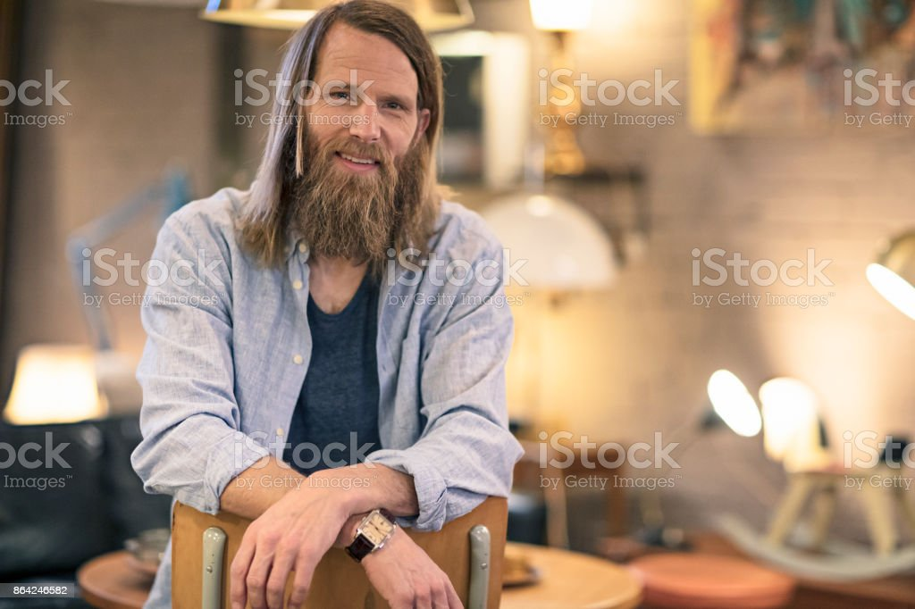 Portrait of a male business owner sitting in his furniture store royalty-free stock photo