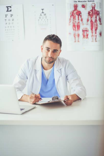 Porträt eines männlichen Arztes mit Laptop am Schreibtisch in Arztpraxis – Foto