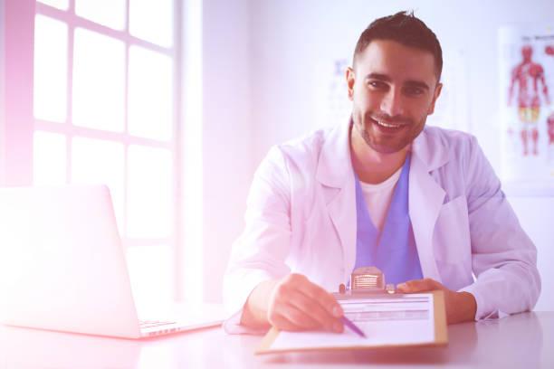 Porträt eines männlichen Arztes mit Laptop am Schreibtisch im Arztbüro – Foto