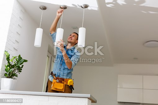 Portrait Of A Male Electrician Fixing Light On Ceiling
