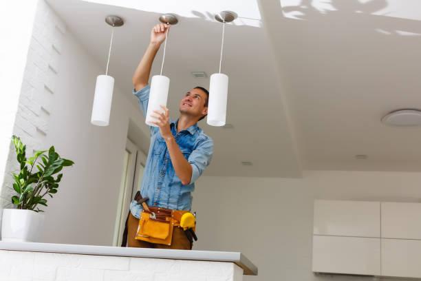 portret van een mannelijke elektricien fixing licht op plafond - menselijke vinger stockfoto's en -beelden