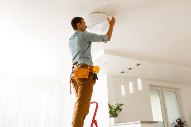 Portrait Of A Male Electrician Fixing Light On Ceiling stock photo