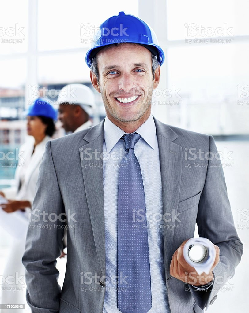 Portrait of a male engineer holding blueprints royalty-free stock photo
