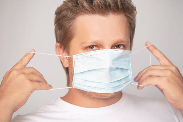 Portrait of a man adult young in a medical mask on an isolated background stock photo