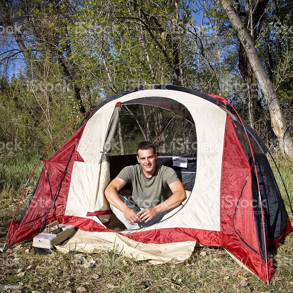 Portrait of a man camping sitting in a red tent smiling royalty-free stock photo