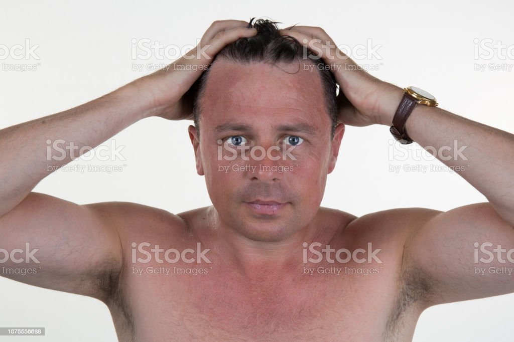 Portrait of a man combing his hair with hands стоковое фото