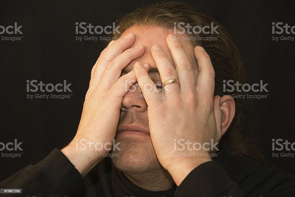 Portrait of a man covering his face with hand royalty-free stock photo