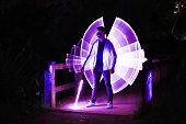 Boy with a mask and a lightsaber and virtual wings, standing on a wooden bridge at night
