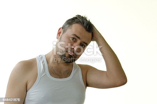 istock Portrait of a man in a white T-shirt, straightens hair with his hand 648401876