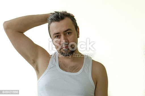 istock Portrait of a man in a white T-shirt, straightens hair with his hand 648401886
