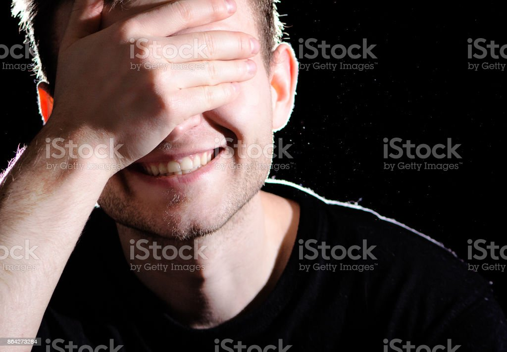 portrait of a man on a  black background, smiling with beautiful smile, covering his eyes with his hand, white teeth royalty-free stock photo